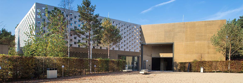 Zdjęcie przedstawia budynek muzealny od strony placu, w letniej porze.