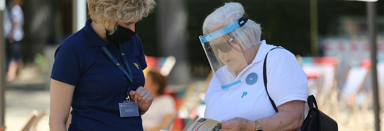 pracowniczka Muzeum przygląda się wraz z wolontariuszką, osobą w wieku emerytalnym, folderowi muzealnemu.