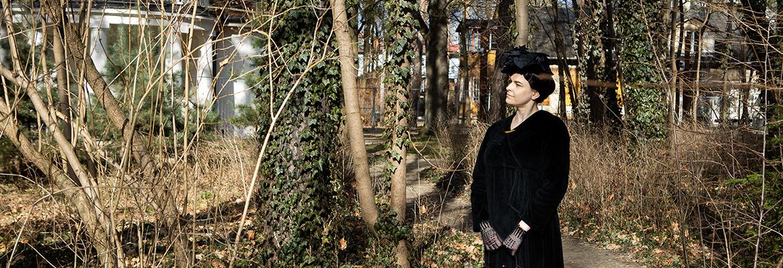Kobieta w czarnej sukni i kapeluszu z początku XX wieku stoi przed dworkiem Milusin. Zdjęcie zrobione współcześnie