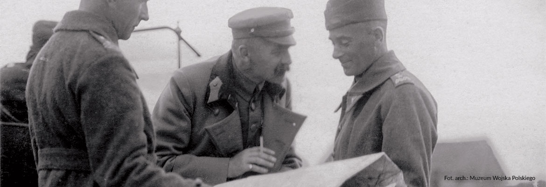 Józef Piłsudski z papierosem i mapą w ręku wyjaśnia oficerowi rozkaz