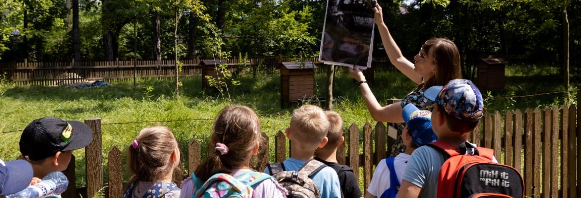 Edukatorka pokazuje grupie dzieci w wieku wczesnoszkolnym tablet. Grupa przebywa w ogrodzie dworku Milusin, pora letnia