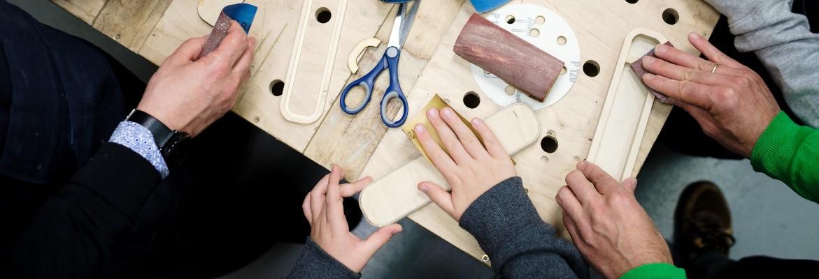 Na stole leżą nożyczki, papier ścierny, drewniane elementy. Sięgają po nie dłonie osób w różnym wieku